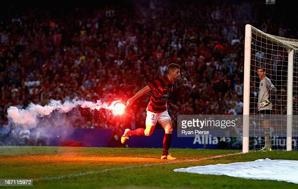 Shannon Cole of the Wanderers removes a flare from the pitch during the ALeague 2013 Grand Final match between the Western Sydney Wanderers and the...