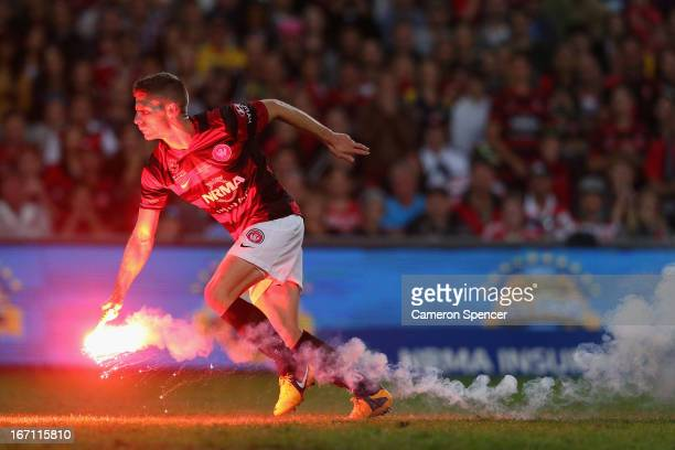 Shannon Cole of the Wanderers removes a flare off the pitch during the ALeague 2013 Grand Final match between the Western Sydney Wanderers and the...