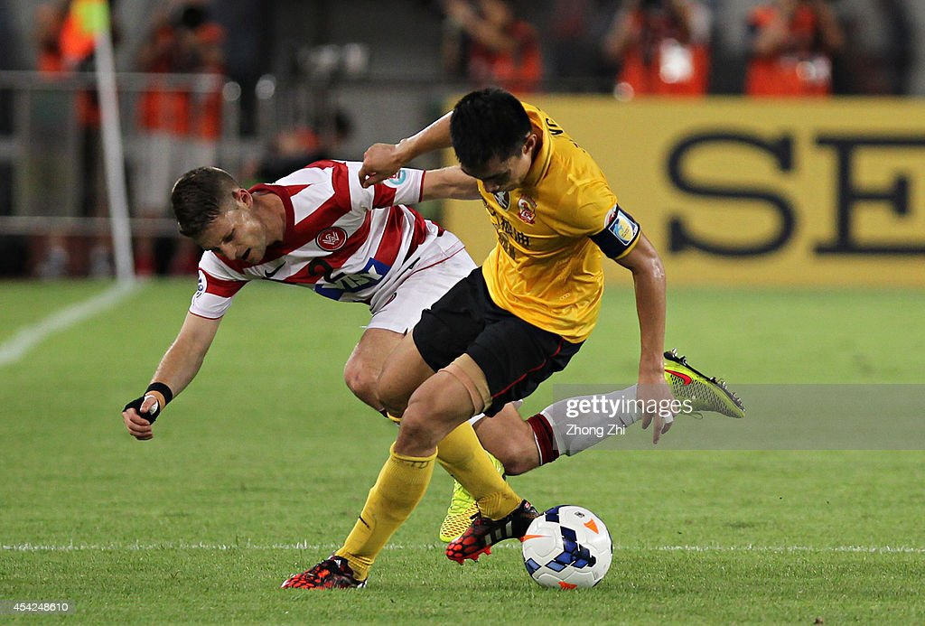 Shannon Cole of Western Sydney Wanderers competes the ball with Zheng Zhi of Guangzhou Evergrande during the Asian Champions League Quarter Final match between the Western Sydney Wanderers and Guangzhou Evergrande at Tianhe Sports Center on August 27, 2014 in Guangzhou, China.