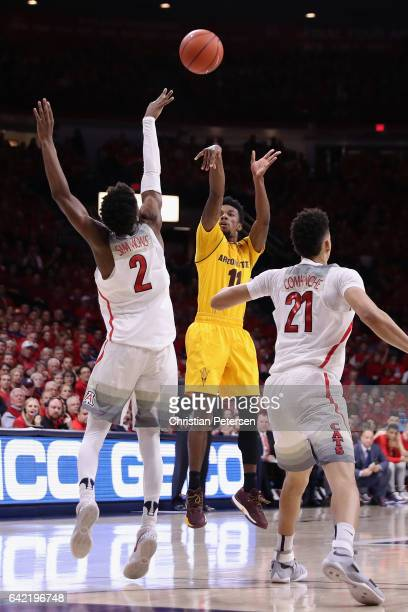 Shannon Evans II of the Arizona State Sun Devils attempts a shot over Kobi Simmons and Chance Comanche of the Arizona Wildcats during the second half...