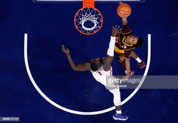 Shannon Evans II of the Arizona State Sun Devils shoots over Rawle Alkins of the Arizona Wildcats during the second half of the college basketball...