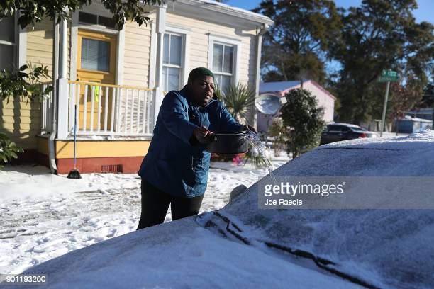 Shannon Fields uses cold water to try and remove the ice from her cars windshield as snow that fell yesterday and cold weather blanket the area on...