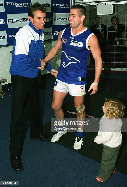 Shannon Grant for the Kangaroos is congratulated by coach Dean Laidley after completing his 250th game in the round 13 AFL match between the...