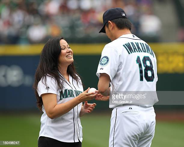 Shannon Lee daughter of martial arts legend Bruce Lee is greeted by pitcher Hisashi Iwakuma of the Seattle Mariners after throwing out the ceremonial...
