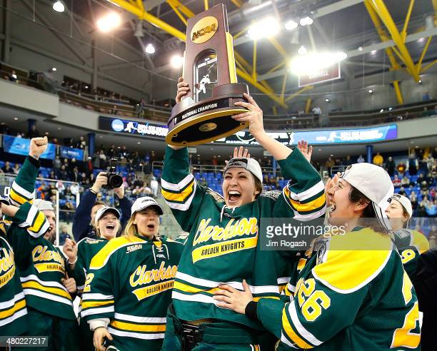 Shannon MacAulay of the Clarkson Golden Knights who scored the winning goal against the Minnesota Golden Gophers holds up the championship trophy...