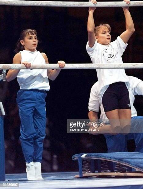 Shannon Miller currently number one and number two Dominique Moceanu warm up on the uneven bars before the start of the Women's Optionals at the 1996...