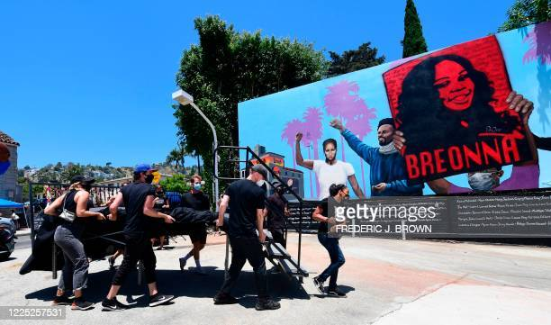 Shannon Morton leads a group of people helping to carry a stage at the unveiling of a 148footlong mural as a tribute to Black Lives Matter on July 7...