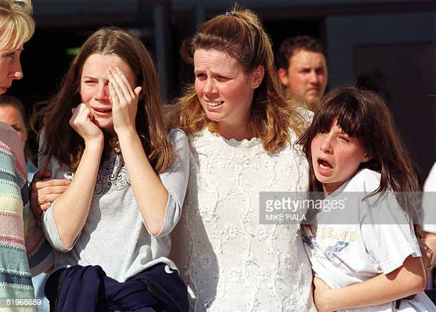 Shannon Ray comforts her daughters Sierra Smith and Ashley Smith after they were reunited following a hostage taking 24 October at Pioneer Elementary...