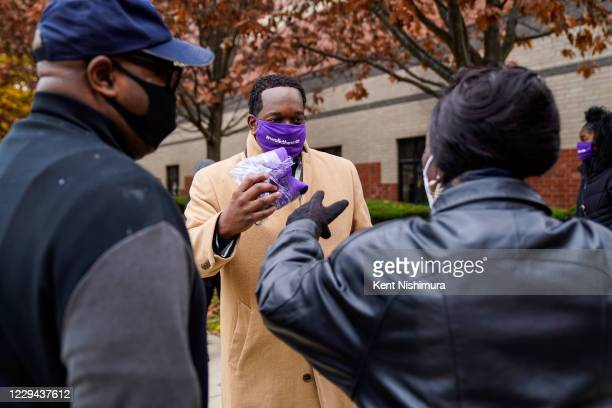 Shannon Rochon of Detroit hands out masks as he speaks with people participating in a Walk The Vote event at Greater Grace Temple on Sunday, Nov. 1,...