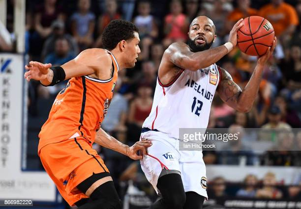 Shannon Shorter of the 36ers looks to pass past Michael Carrera of the Taipans during the round four NBL match between the Cairns Taipans and the...