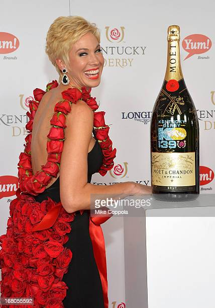 Shannon Voss wearing the 2013 Rose Dress designed by Amy Streeter signs the Moet Chandon 6L for the Churchill Downs Foundation during the 139th...