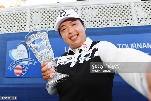 Shanshan Feng of China imitates a selfie as she poses with the trophy after winning the TOTO Japan Classics 2017 at the Taiheiyo Club Minori Course...