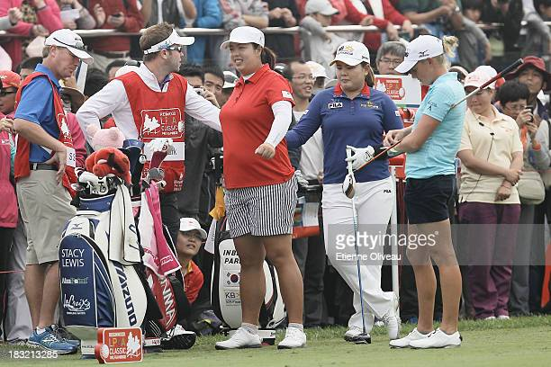 Shanshan Feng of China Inbee Park of South Korea and Stacy Lewis of United States wait on the range with their caddies during the final round of the...