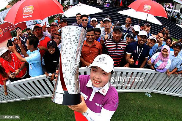 Shanshan Feng of China lifts the Sime Darby LPGA trophy aloft in front of cheering fans after she won it 17 under par 267 during day four of the Sime...