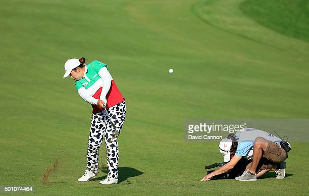 Shanshan Feng of China plays her second shot on the par 4 14th hole despite the close attention of the German Television company UCON's cameraman...