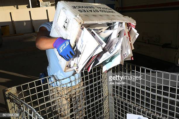 Shantel Hill a City Carrier Assistant to the United States Postal Service works to unload her mail truck at the Processing and Distribution Center...