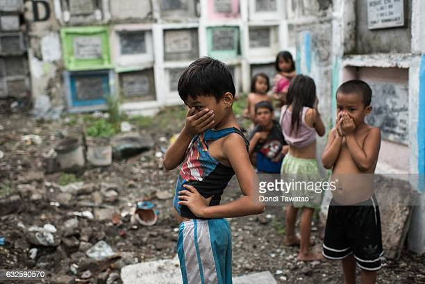 Shanty dwellers living inside the cemetery look at bodies being buried on January 24 2017 in Manila Philippines Many bodies of victims of...