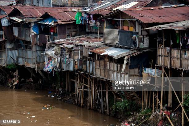 TOPSHOT Shanty houses with hanging toilets with waste that runs straight into the river below are seen in downtown Jakarta on November 14 2017 / AFP...