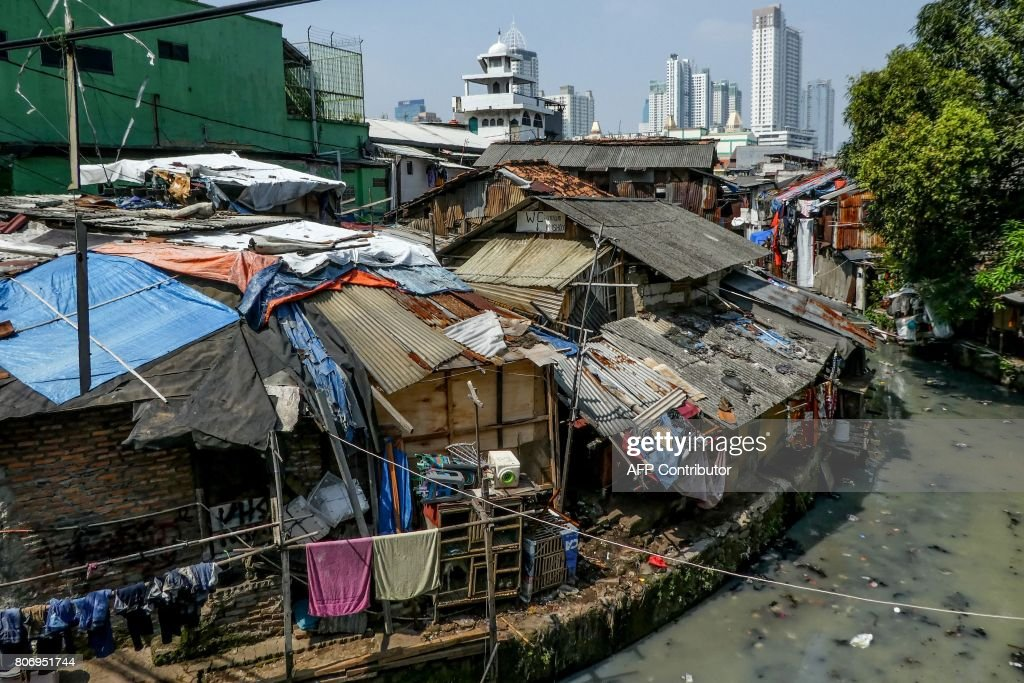 Shantyhouses are seen as buildings loom in the background in Jakarta on July 4, 2017. /