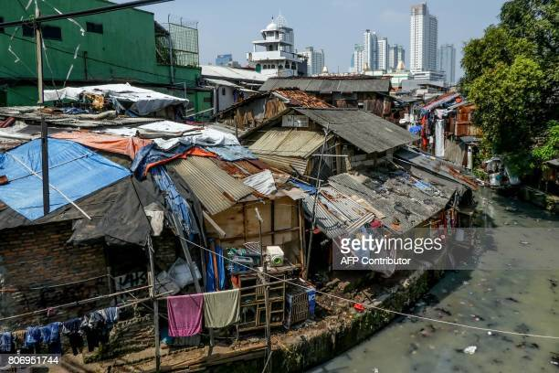 Shantyhouses are seen as buildings loom in the background in Jakarta on July 4 2017 / AFP PHOTO / BAY ISMOYO