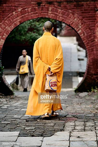 Shaolin monk holding fast-food bag behind back, outside temple entrance