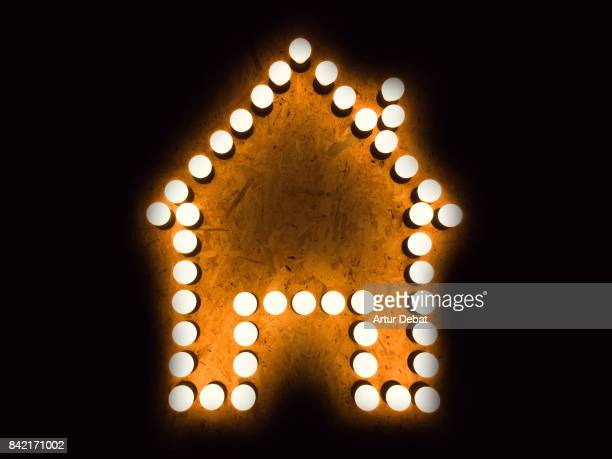 Shape of house made with bright light bulbs in a wall with black background.