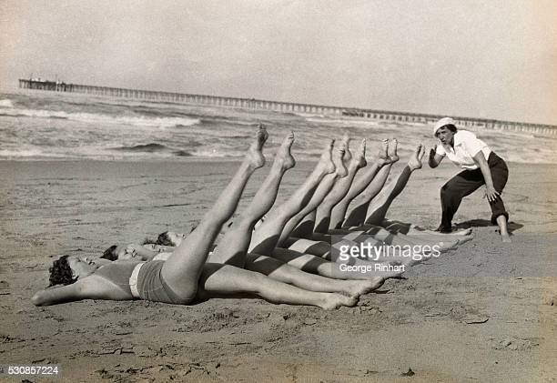 Shapely members of Mrs Sue Robinson's chores obey her instructions cheerfully in a workout on the sunlit beach at El Segundo while New York Chorines...