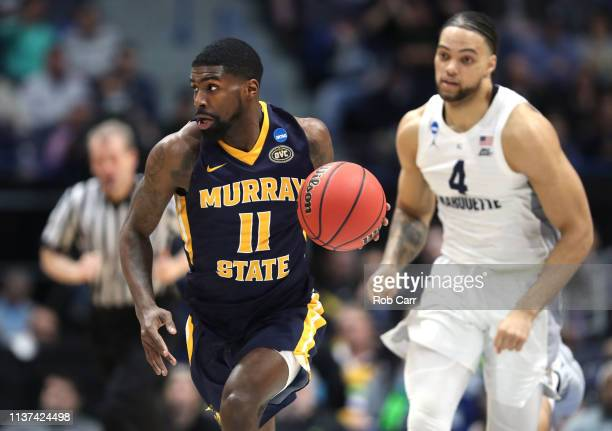 Shaq Buchanan of the Murray State Racers drives the ball away from Theo John of the Marquette Golden Eagles during the first round game of the 2019...