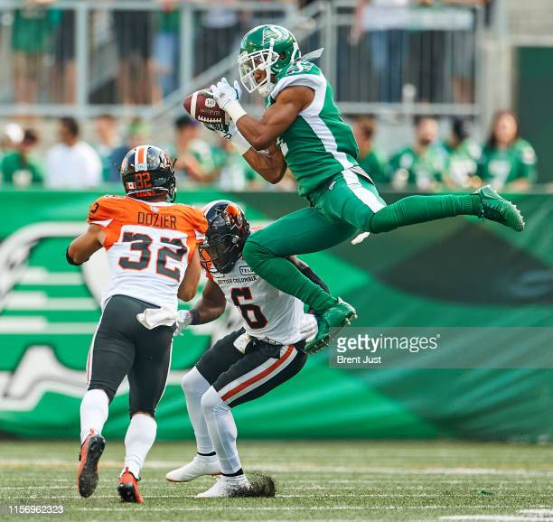 Shaq Evans of the Saskatchewan Roughriders goes up to make a catch between TJ Lee and Branden Dozier of the BC Lions in the first half of the game...