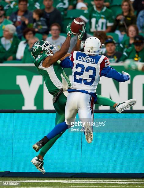 Shaq Evans of the Saskatchewan Roughriders goes up to make a catch over Tommie Campbell of the Montreal Alouettes in the game between the Montreal...