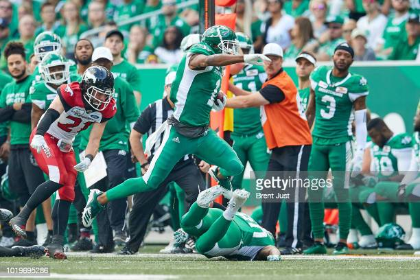 Shaq Evans of the Saskatchewan Roughriders leaps over a fallen teammate while running after a catch in the game between the Calgary Stampeders and...