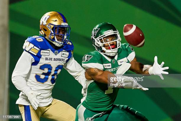 Shaq Evans of the Saskatchewan Roughriders makes a catch for a touchdown behind Winston Rose of the Winnipeg Blue Bombers that was called back on a...