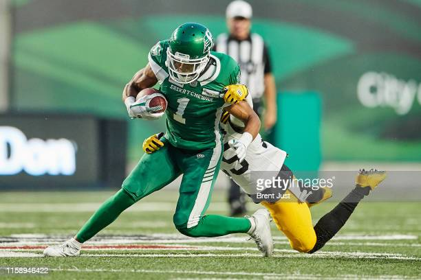 Shaq Evans of the Saskatchewan Roughriders tries to shed Jumal Rolle of the Hamilton Tiger-Cats after making a catch in the game between the Hamiton...