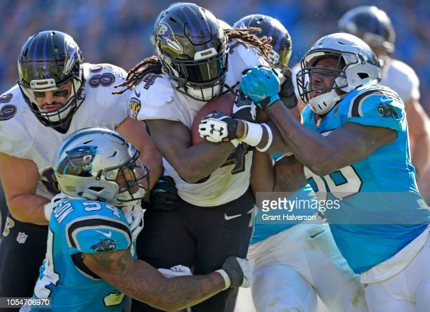 Shaq GreenThompson and Thomas Davis of the Carolina Panthers tackle Alex Collins of the Baltimore Ravens during their game at Bank of America Stadium...