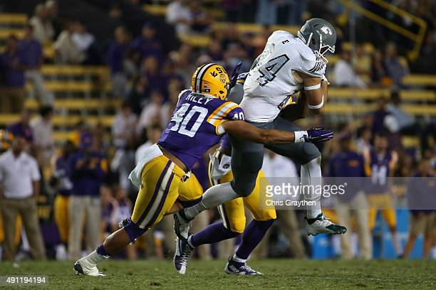 Shaq Vann of the Eastern Michigan Eagles is tackled by Duke Riley of the LSU Tigers at Tiger Stadium on October 3 2015 in Baton Rouge Louisiana