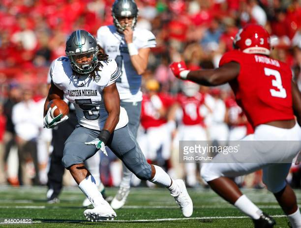 Shaq Vann of the Eastern Michigan Eagles runs for yards against Olakunle Fatukasi of the Rutgers Scarlet Knights during the first quarter of a game...
