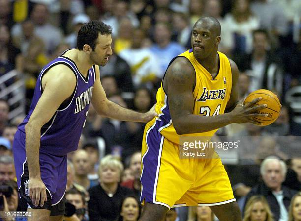 Shaqauille O'Neal of the Los Angeles Lakers is guarded by Vlade Divac of the Sacramento Kings during the game between the Sacramento Kings and the...