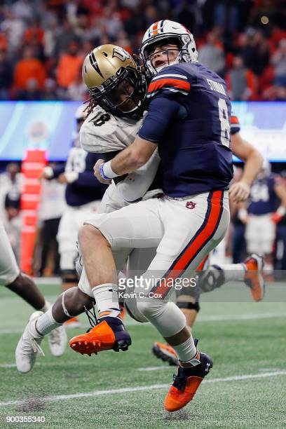 Shaquem Griffin of the UCF Knights hits Jarrett Stidham of the Auburn Tigers in the second half during the ChickfilA Peach Bowl at MercedesBenz...