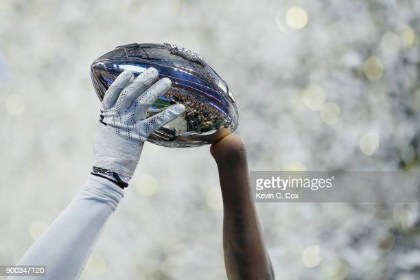 Shaquem Griffin of the UCF Knights holds the trophy after defeating the Auburn Tigers 3427 to win the ChickfilA Peach Bowl at MercedesBenz Stadium on...