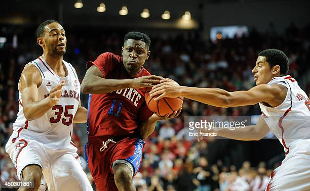 Shaquiell Mitchell of the South Carolina State Bulldogs drives between David Rivers and Walter Pitchford of the Nebraska Cornhuskers during their...