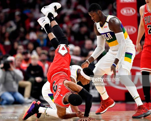 Shaquille Harrison of the Chicago Bulls falls over Tim Frazier of the New Orleans Pelicans at United Center on February 06 2019 in Chicago Illinois...