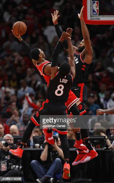 Shaquille Harrison of the Chicago Bulls puts up a shot against Greg Monroe and Jordan Loyd of the Toronto Raptors at United Center on November 17...