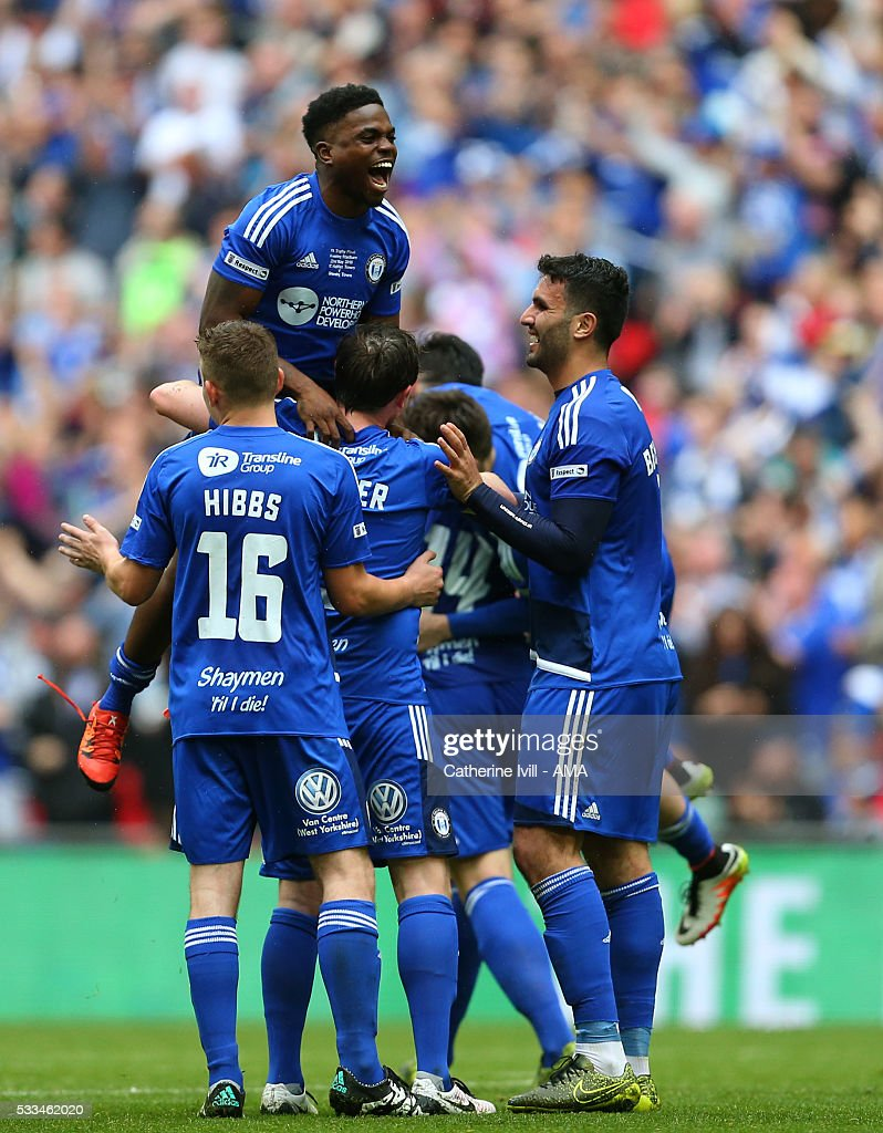 Shaquille McDonald of Halifax Town jumps up on his team mates as the team celebrate the win after The FA Trophy Final match between Grimsby Town and Halifax Town at Wembley Stadium on May 22, 2016 in London, England.