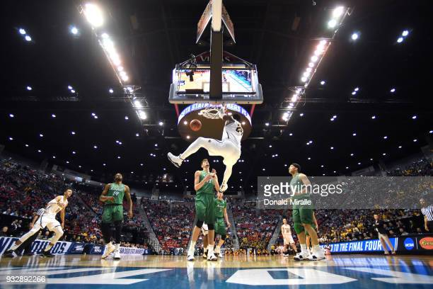 Shaquille Morris of the Wichita State Shockers dunks against Ajdin Penava of the Marshall Thundering Herd in the first half during the first round of...