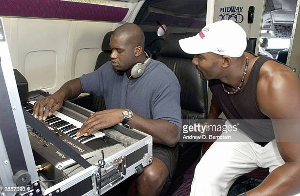 Shaquille O'Neal and Karl Malone of the Los Angeles Lakers play with a keyboard on the plane headed to training camp October 2 2003 in Honolulu...