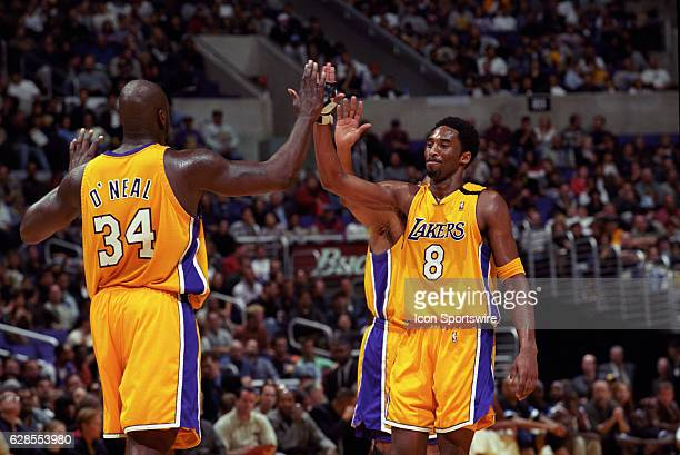 Shaquille O'Neal and Kobe Bryant of the Los Angeles Lakers high five each other during a National Basketball Association game against the Orlando...
