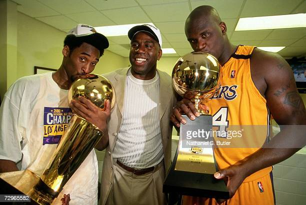 Shaquille O'Neal and Kobe Bryant of the Los Angeles Lakers pose with Lakers legend Magic Johnson after winning the NBA Championship trophy after...