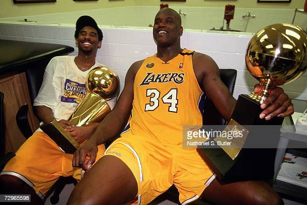 Shaquille O'Neal and Kobe Bryant of the Los Angeles Lakers sit with the NBA Championship and MVP trophies after defeating the Indiana Pacers in Game...