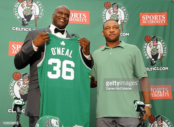 Shaquille O'Neal holds up his new jersey alongside head coach Doc Rivers of the Boston Celtics August 10 2010 at the Boston Celtic training facility...
