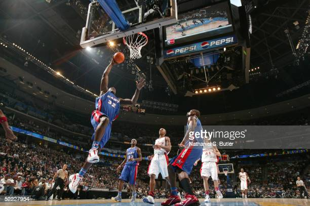 Shaquille O'Neal of the Eastern Conference AllStars goes up for a dunk as O'Neal's East Teammates LeBron James and Dwyane Wade look on as well as Ray...